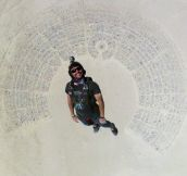 Fantastic shot of man skydiving into Burning Man…