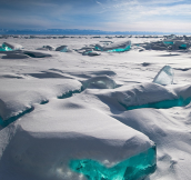 Due to a natural phenomenon, temperature, wind and sun cause the ice crust to crack and form beautiful turquoise blocks or ice hummocks on the surface of Lake Baikal in Siberia.