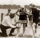 An beach official measures bathing suits to ensure they aren't too short 1920s