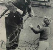 An East German soldier ignores orders to let no one pass and helps a boy, who was found on the opposite side from his family, cross the newly formed 'Berlin Wall'- 1961