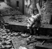 An English girl comforts her doll in the rubble of her bomb-damaged home, 1940