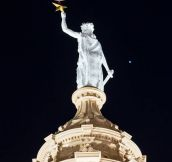 Blood moon supported by the Goddess of Liberty.