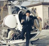 Frank Sinatra stepping off of a helicopter with a drink in his hand, by Yul Brynner, 1964.