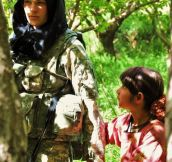 A Curious Afghan Girl Holds The Hand Of An American Soldier