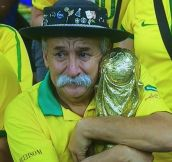 Old man with a mustache hugging a world cup while watching Brasil lose
