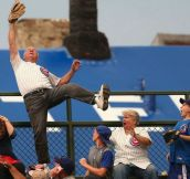 65 year old Man Catching a homerun ball in front of the railings in the Wrigley Field Bleachers.