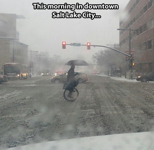 funny-winter-snow-unicycle-umbrella-street