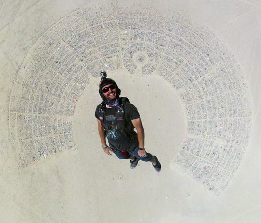 Fantastic shot of man skydiving into Burning Man…