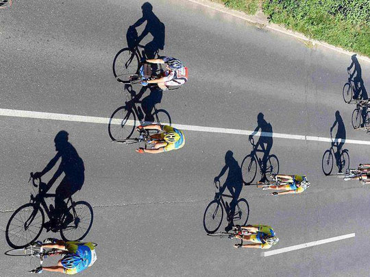 Cyclists As Shadows To Their Bikes