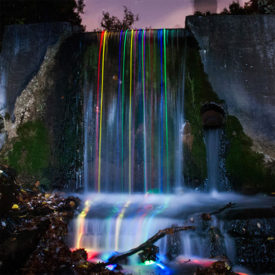 Long Exposure Shot Of Glow Sticks Dropped Into A Waterfall