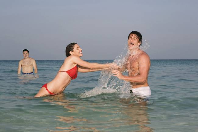 Asia, Thailand, Young Couple in ocean, splashing water