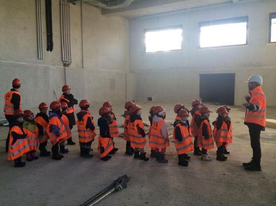 A bunch of kiddos getting a tour on a tech site