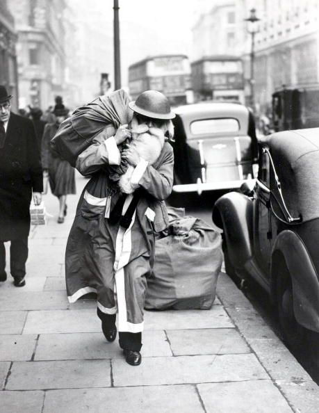 Father Christmas with helmet delivers presents during the London Blitz-1940