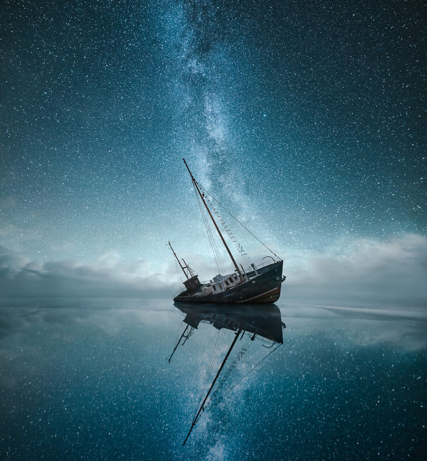 Starry night sky over clam waters.