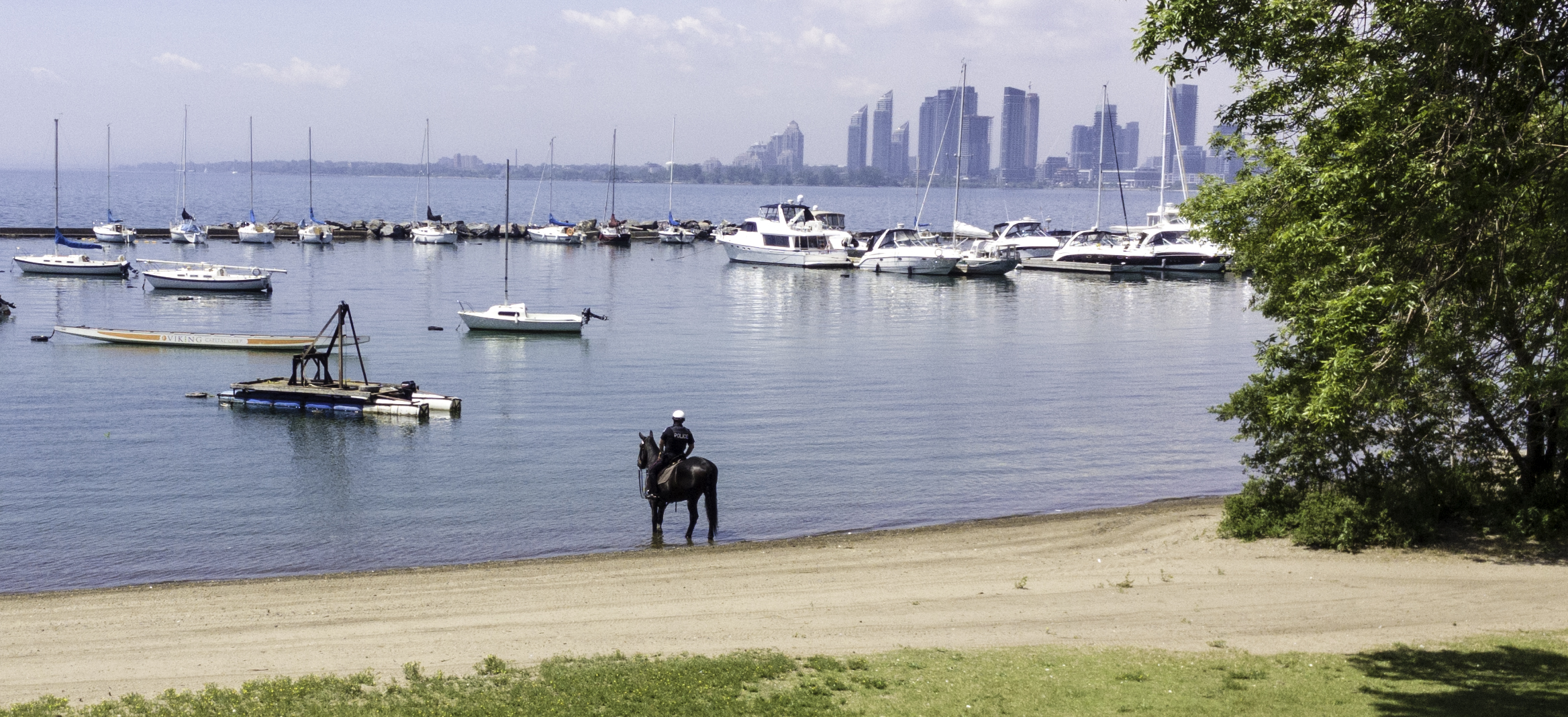 This police officer let his horse stand in the lake to cool his feet down, and talked to him the whole time they stood there.