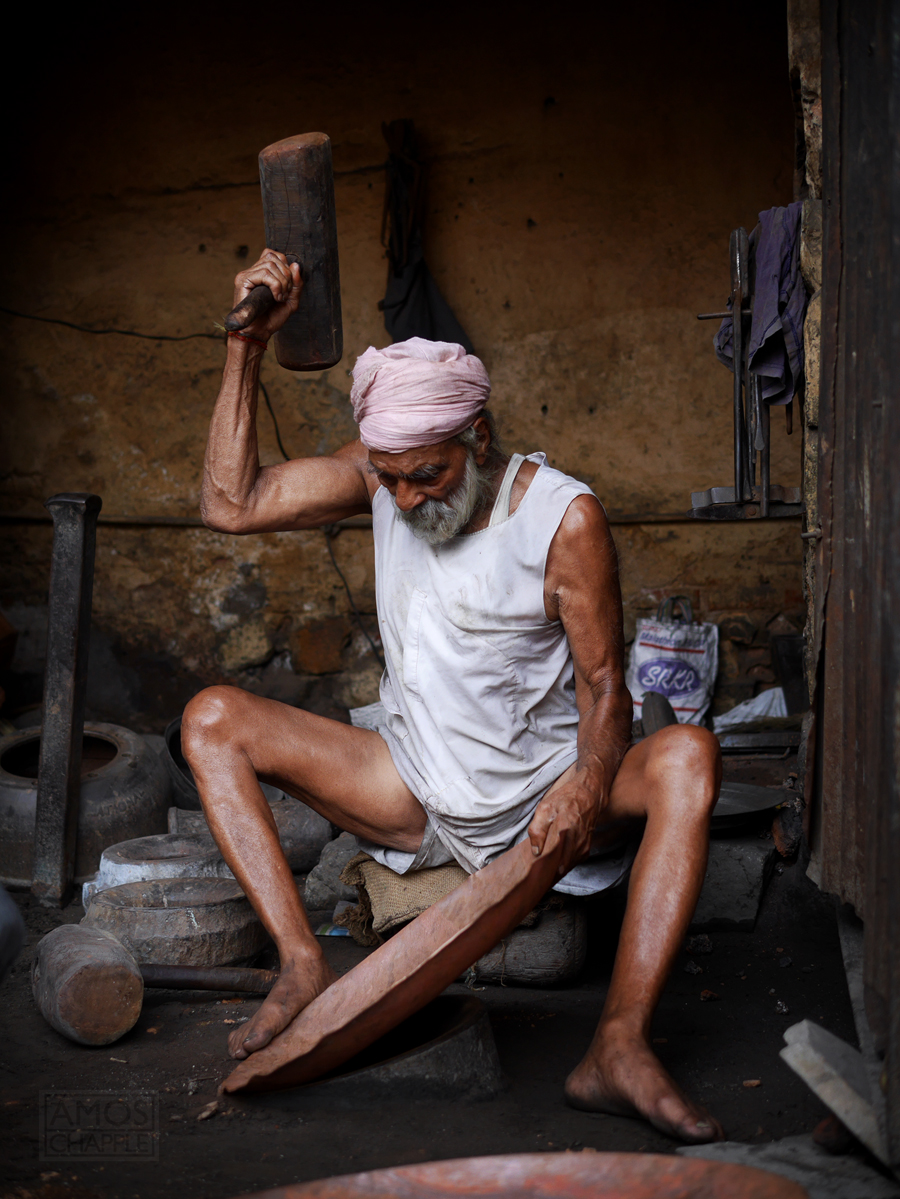 Eighty one year-old Sikh man hammering a cooking pot into shape.