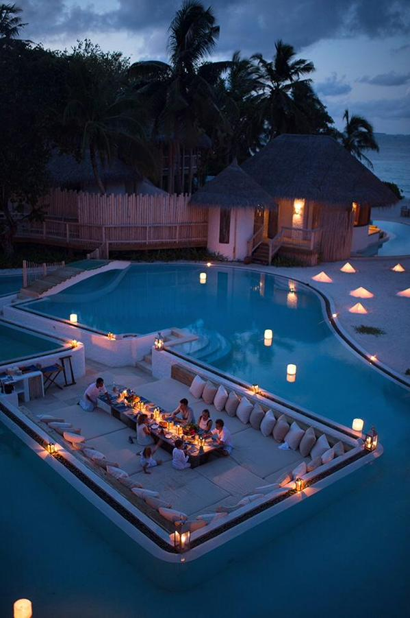 Having dinner surrounded by a swimming pool