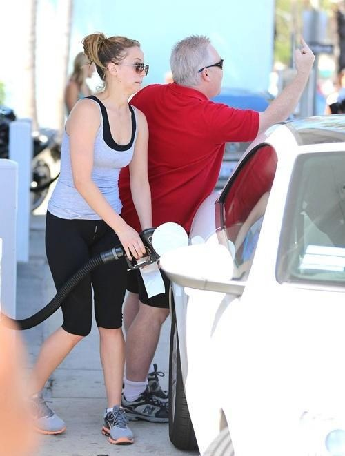 Jennifer Lawrence pumping gas while her dad salutes the paparazzi