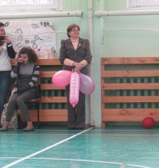 8 This teacher holding some balloons.