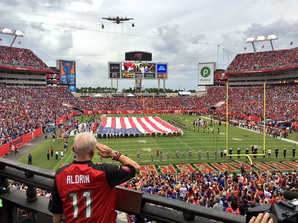 Buzz Aldrin saluting the flag at a football game with a military flyover