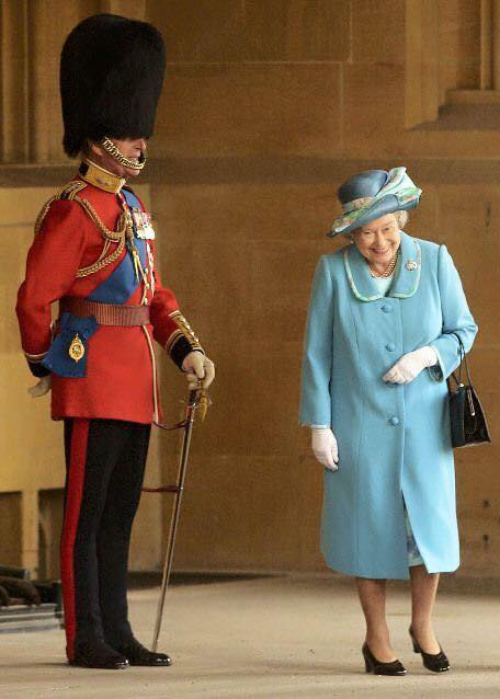 The Queen cracks up when she realizes the man in uniform is actually her husband