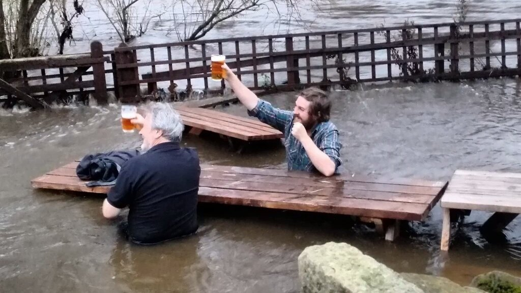 Two chaps enjoy a pint in a flooded beer garden in Leeds