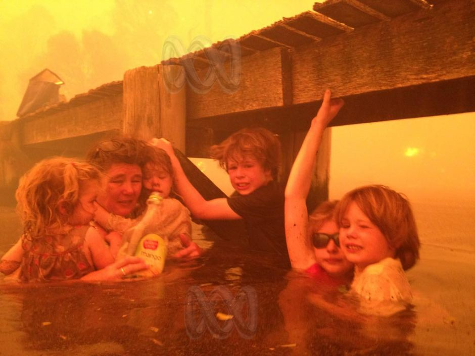 Family take shelter in a river as a bushfire rages across their farm