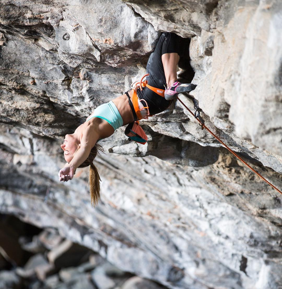 Rock climber Courtney Woods rests her arms during a climb in Flatanger, Norway