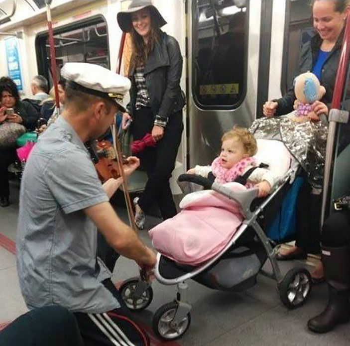 Man spent his subway ride playing his violin for a baby it was crying