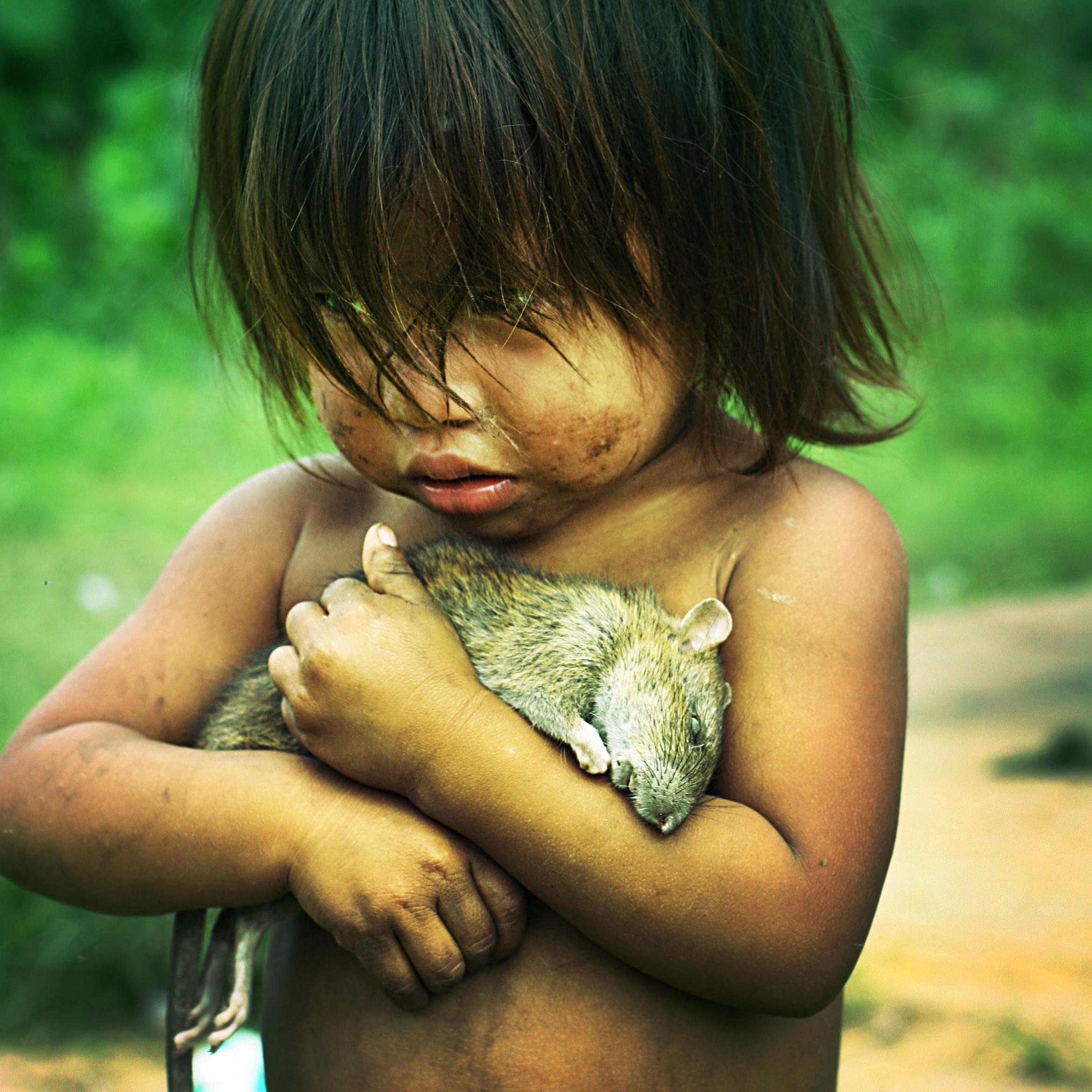 Little Guarani Girl Holds On Tight To A Dead Rat