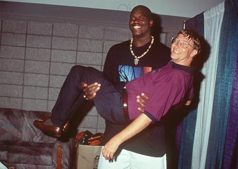 Shaquille O'neal holding $78 billion in small bills.