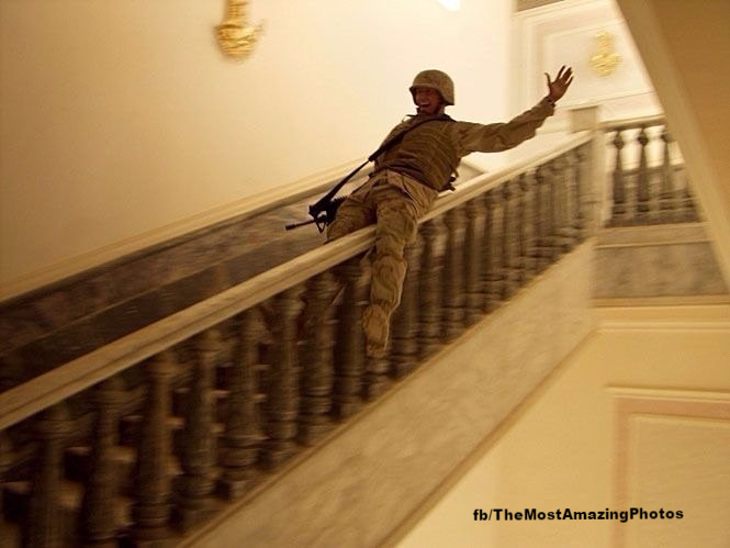 U.S. soldier slides down a bannister in one of Saddam Hussein's palaces